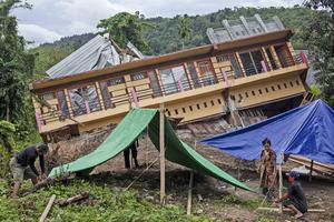Residents build tents outside their badly damaged house in Mamuju (Yusuf Wahil/AP)