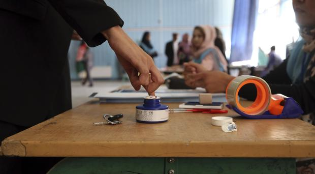 An Afghan woman links her finger at a polling station at Amani high school, near the presidential palace in Kabul (AP)