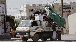 A Yemeni man loads his belongings into a truck in Sanaa as people flee in fear of clashes rashes between the Saudi-led coalition and Shiite rebels (AP)