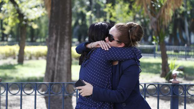 The partner of a member of the crew and a friend comfort each other in Mexico City (Rebecca Blackwell/AP)