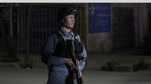An Afghan policeman stands guard at Kabul's Park Palace Hotel after an attack by Taliban militants