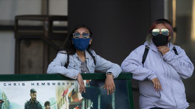 People wear masks as they wait for a bus in Los Angeles (Damian Dovarganes/AP)