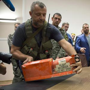 A pro-Russian fighter hands over a black box from the crashed Malaysia Airlines Flight 17 to Malaysian representatives in Donetsk (AP)