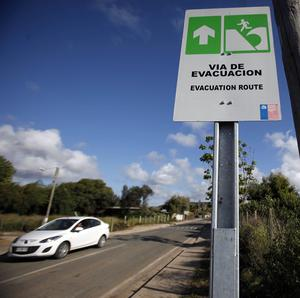 A car drives by a sign indicating the evacuation route in the event of a tsunami, in Navidad, Chile (AP)
