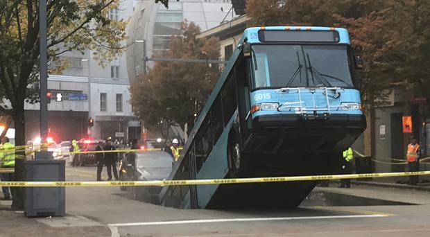 Authorities are investigating after a Port Authority bus was caught in a sinkhole in Pittsburgh (Darrell Sapp/Pittsburgh Post-Gazette via AP)