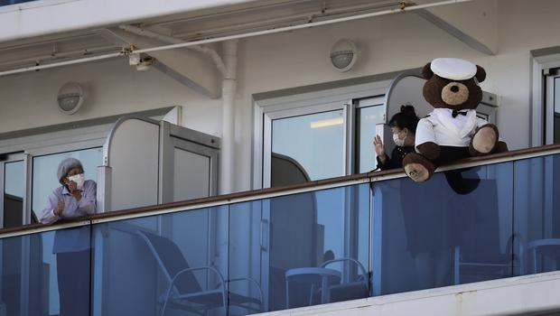 A woman with a teddy bear waves to another passenger quarantined on the Diamond Princess cruise ship (Jae C Hong/AP)