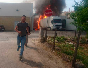 Two imagess from the Facebook page of Fabio Miguel show smoke rising behind a Lidl supermarket near Lisbon, after a small plane crashed, killing four people on board