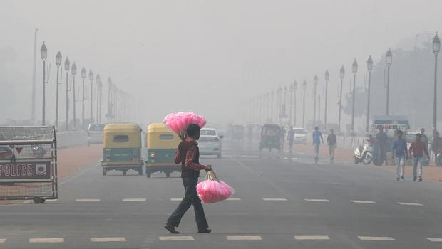 A sweet seller walks amidst thick layer of smog (Manish Swarup/AP)
