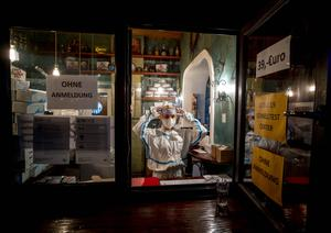 A medical worker waits for customers at a corona quick test center that is located in an empty tequila bar in Frankfurt (AP/Michael Probst)