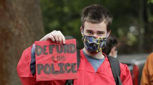 """Elliot Armitage, a 2020 graduate of Ballard High School, holds his mortarboard cap that reads """"Defund the Police"""" as he prepares to take part in a cap and gown Black Lives Matter march with other high school graduates in Seattle (Ted S Warren/AP)"""