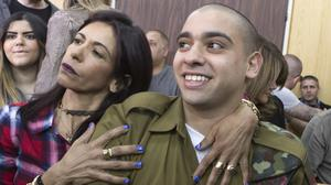 File picture showing Israeli soldier Elor Azaria being embraced by his mother at the start of his sentencing hearing (AP)