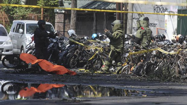 Police inspect wrecked motorcycles outside a church in Surabaya, East Java (Trisnadi/AP)