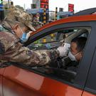 A security guard tests a driver's temperature at a checkpoint at a highway toll gate in Wuhan on Thursday (Chinatopix/AP)