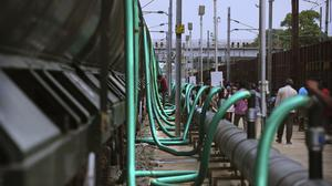 Hosepipes are used to fill train wagons with drinking water piped in from the Mettur dam on the Cauvery River, at Jolarpet railway station (Manish Swarup/AP)