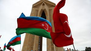 Azerbaijanis wave national flags as they celebrate entry of troops into Aghdam (Aziz Karimov/AP)