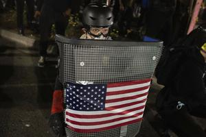 A protester holds a homemade riot shield (Christian Monterrosa/ AP)