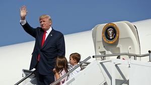 President Donald Trump waves as he walks down the steps of Air Force One with his grandchildren, Arabella Kushner, center, and Joseph Kushner, right, after arriving at Morristown Municipal Airport to begin his summer vacation at his Bedminster golf club (AP)