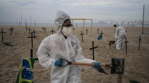 Activists in costume dig symbolic graves on Copacabana beach as a protest against the government's handling of the COVID-19 pandemic (Leo Correa/AP)