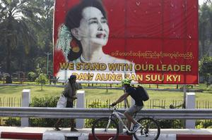 A cyclist rides past a sign with an image of Myanmar leader Aung San Suu Kyi in Yangon on Friday. Reports say Ms Suu Kyi has been placed under house arrest (Thein Zaw/AP)