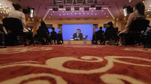 Journalists attend a news conference by Zhang Yesui, a spokesman for the National People's Congress, broadcast remotely to the media center on the eve of the annual legislature opening session in Beijing (Mark Schiefelbein, Pool/AP)