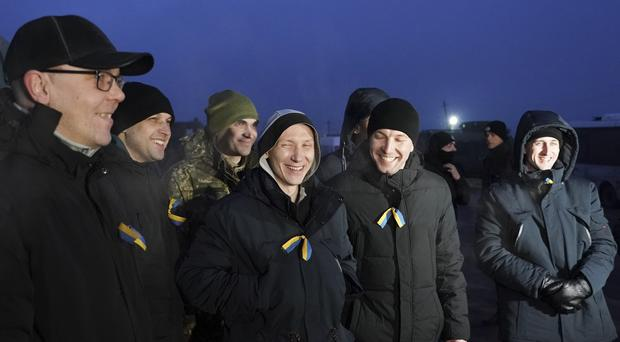 Ukrainian war prisoners smile as they wait for a bus to be transferred to an airport (Evgeniy Maloletka/AP)
