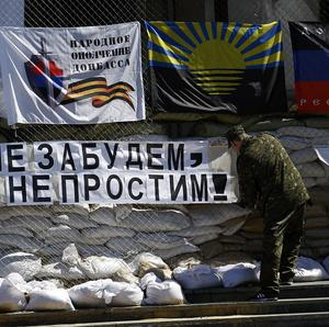 "A pro-Russian gunman hangs a banner that reads: ""Do not forget, do not forgive!"" in front of the city hall in Slovyansk, eastern Ukraine (AP)"