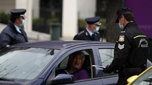 A traffic police officer checks a driver for valid documents following a lockdown order by the government in Athens (Thanassis Stavrakis/AP)