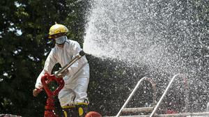 A firefighter sprays disinfectant from the fire engine in hopes of curbing the spread of the new coronavirus in Burma (AP)
