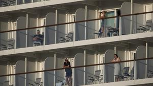 Passengers of the Mein Schiff 6 cruise ship stand outside their cabins as the ship is docked at Piraeus port, near Athens on Tuesday, Sept. 29, 2020. Greek authorities say 12 crew members on a Maltese-flagged cruise ship carrying more than 1,500 people on a Greek islands tour have tested positive for coronavirus and have been isolated on board. (AP Photo/Petros Giannakouris)