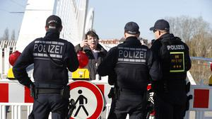 Police officers prevent a woman from entering Germany at the border with France (Jean-Francois Badias/AP)