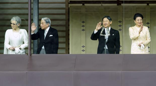 Japan's Emperor Naruhito and Empress Masako, at right, along with former emperor Akihito and his wife Michiko, wave to crowds from the Imperial Palace on THursday (Eugene Hoshiko/AP)