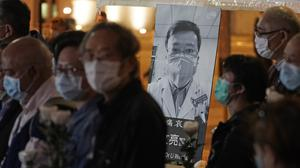 People attend a Hong Kong vigil last month for the late Dr Li Wenliang, who has been exonerated after being reprimanded for warning about the outbreak of the coronavirus (Kin Cheung/AP)