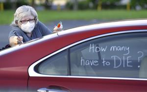 Registered Nurse Laure Hale writes on her car as she is preparing to take part in a motorcade protest to the Duval County School Board building in Jacksonville (Bob Self/AP)