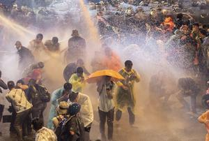 Pro-democracy demonstrators face police water cannon (AP)