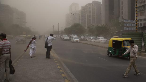 People cross a road, enveloped by dust rising from a storm in New Delhi, India (Manish Swarup.AP)