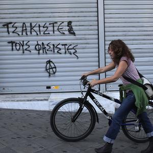 "A woman walks past graffiti reading ""crush the fascists"" in Athens as Greek lawmakers vote on a proposal to suspend state funding for political parties accused of criminal activities (AP)"