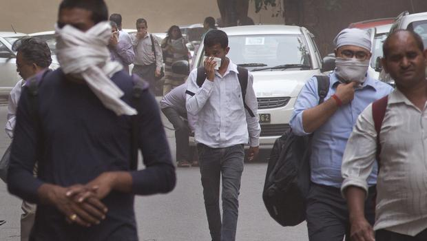 People cover their noses as a dust storm envelops New Delhi (Manish Swarup/AP)