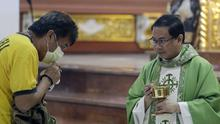 Catholic priest Fr Joseph Arellano, right, looks at a man who forgot to take off his protective mask and tried to insert the host in his mouth during communion at a mass at the Minor Basilica of San Lorenzo Ruiz in Manila's Chinatown, Philippines (Aaron Favila/AP)