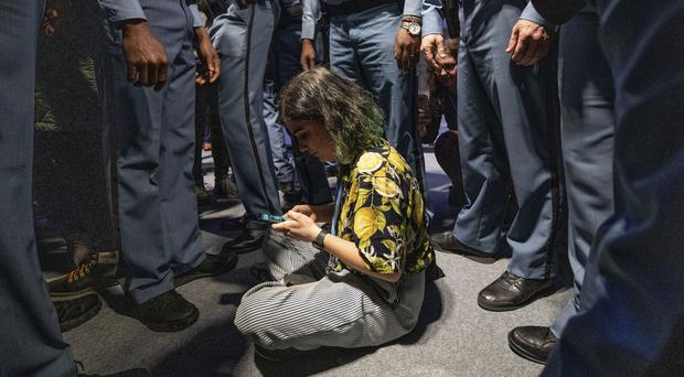 A demonstrator is surrounded by UN security staff members (AP/Bernat Armangue)