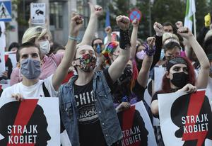 """Protesters with a banner reading """"Women's Strike"""" taking part in a rally against Polish government plans to withdraw from the Istanbul Convention (Czarek Sokolowski/AP)"""