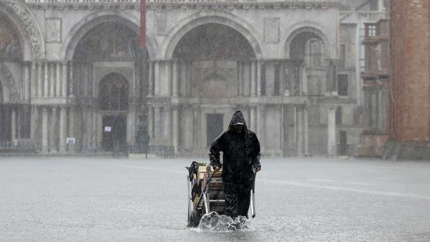 A greengrocer pushes his cart through St Mark's Square (Luca Bruno/AP)