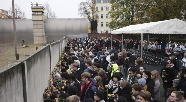 Young people stuck flowers in remains of the Berlin Wall at Bernauer Strasse (Markus Schreiber/AP)