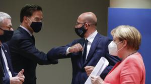 Dutch Prime Minister Mark Rutte, centre left, bumps elbow with European Council President Charles Michel as German Chancellor Angela Merkel walks by as the summit wrapped up (Stephanie Lecocq/Pool/AP)