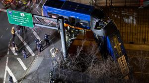 A bus in New York City which careened off a road in the Bronx neighborhood of New York is left dangling from an overpass Friday, Jan. 15, 2021, after a crash late Thursday that left the driver in serious condition, police said. (AP Photo/Craig Ruttle)