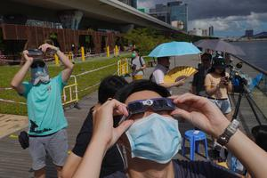 People watch the solar eclipse at a waterfront in Hong Kong (Vincent Yu/AP)