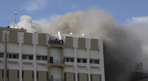 People awaiting rescue stand on the balcony (Rafiq Maqbool/AP)