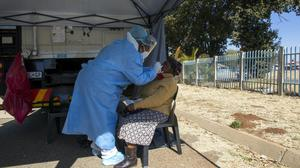 A woman has a sample collected for coronavirus testing during the screening and testing campaign aimed to combat the spread of Covid-19, in Eldorado Park outside of Johannesburg (Themba Hadebe/AP)