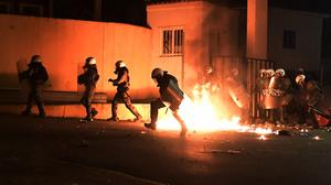 A riot policeman tries to avoid a petrol bomb thrown by protesters (AP/Michael Varaklas)