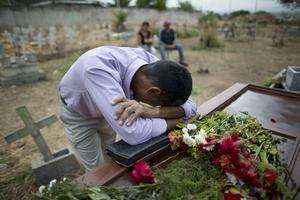 Jesus Zapata cries on the coffin containing the remains of his son Erickson Zapata, at the Municipal Cemetery in Valencia, Venezuela (Ariana Cubillos/AP)