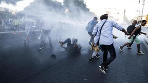 Italian law enforcement officers use water cannons to disperse migrants in Rome (Angelo Carconi/ANSA via AP)